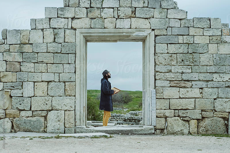 Gypsy Man Stands In  Ancient Wall by Alexander Grabchilev for Stocksy United