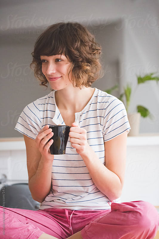 Young woman drinking a cup of tea by michela ravasio for Stocksy United