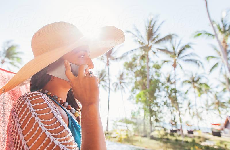 Woman in Beachwear Talking on Phone by VISUALSPECTRUM for Stocksy United