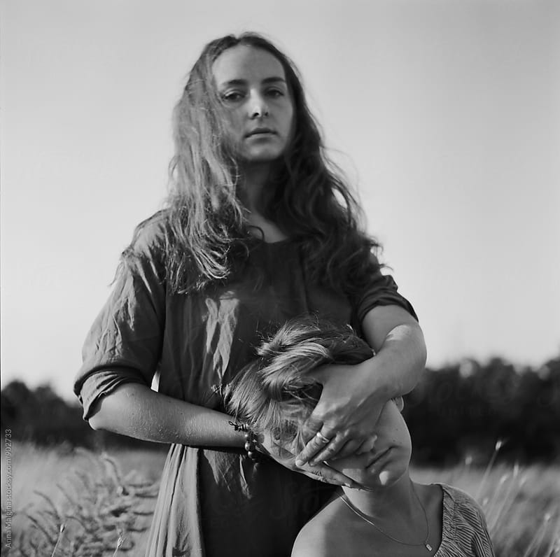 A black and white film portrait of young beautiful woman closing face of her friend by Anna Malgina for Stocksy United