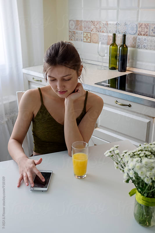 Woman sitting at kitchen table while using smartphone  by Danil Nevsky for Stocksy United