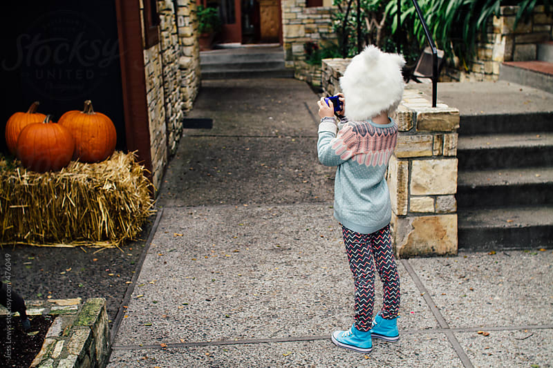 girl taking photo of pumpkin display by Jess Lewis for Stocksy United