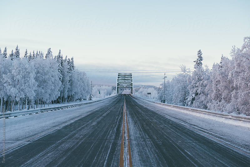 a bridge in Alaska in December from the middle of the road by Tara Romasanta for Stocksy United