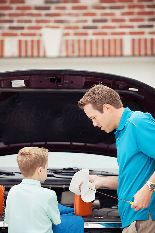 Father: Teaching Child to Check Oil by Sean Locke for Stocksy United