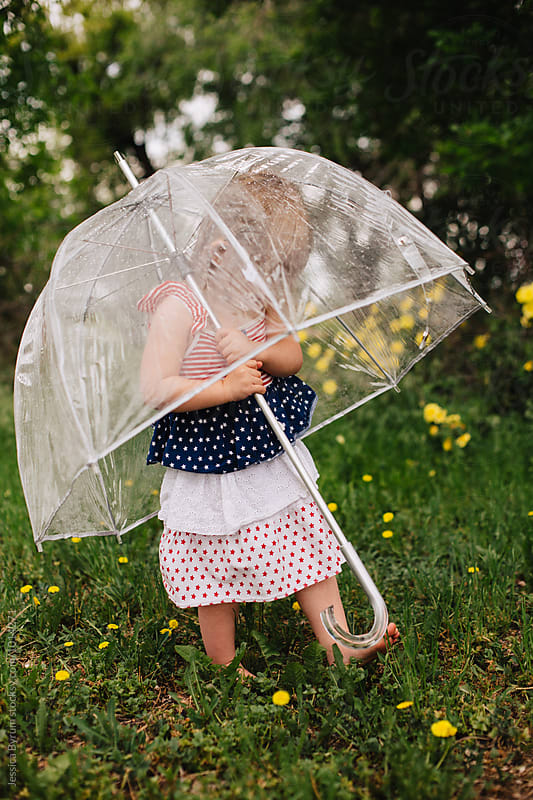 Toddler girl in an American flag dress holding a big, clear umbrella. by Jessica Byrum for Stocksy United