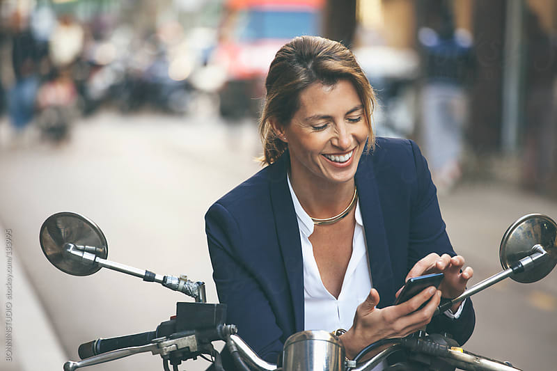 Mature business woman with smartphone on motorbike. Urban street. by BONNINSTUDIO for Stocksy United