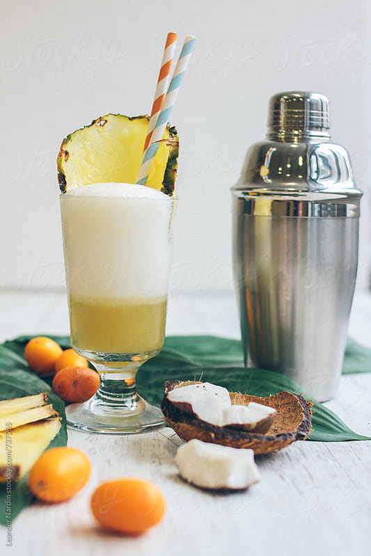 pina colada with typical fruits and a stainless steel shaker on white background by Leander Nardin for Stocksy United