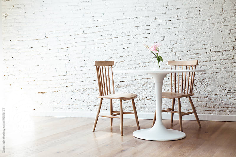 Simple room interior with table and chairs against of white painted room by Vera Lair for Stocksy United