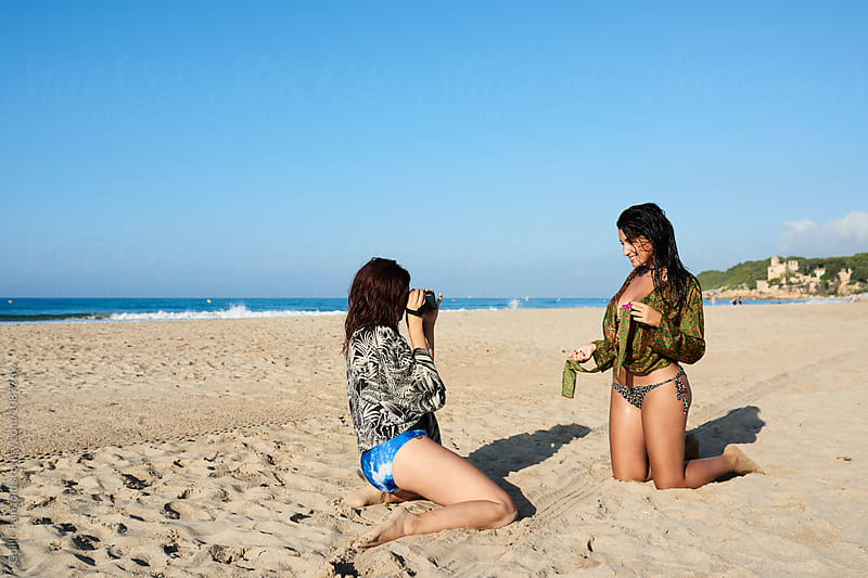 Friends photographing on beach by Guille Faingold for Stocksy United