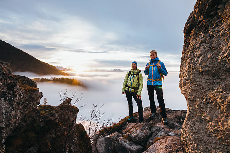 two female hiker above the sea of fog in alpine scenery at sunset by Leander Nardin for Stocksy United