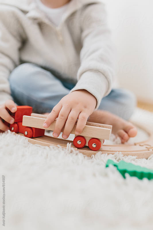 Close-up of little boy playing with toy car by Amir Kaljikovic for Stocksy United