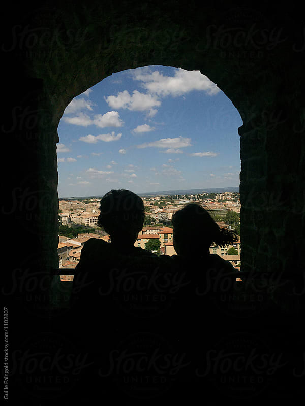 Kids watching cityscape from dark arch window by Guille Faingold for Stocksy United
