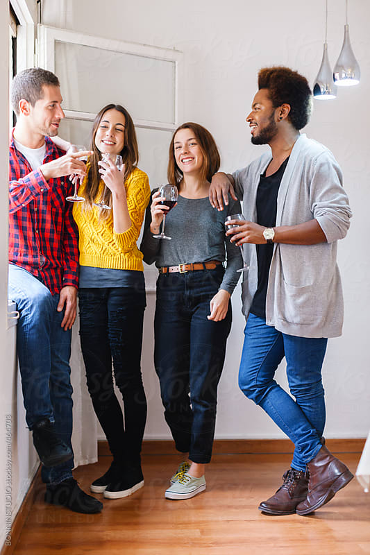 Group of young friends having fun and drinking red wine at home. by BONNINSTUDIO for Stocksy United