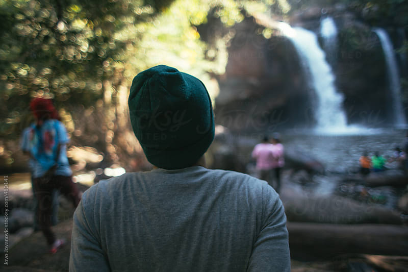 Young man wearing a hat looking out at a waterfall  int he jungle by Jovo Jovanovic for Stocksy United