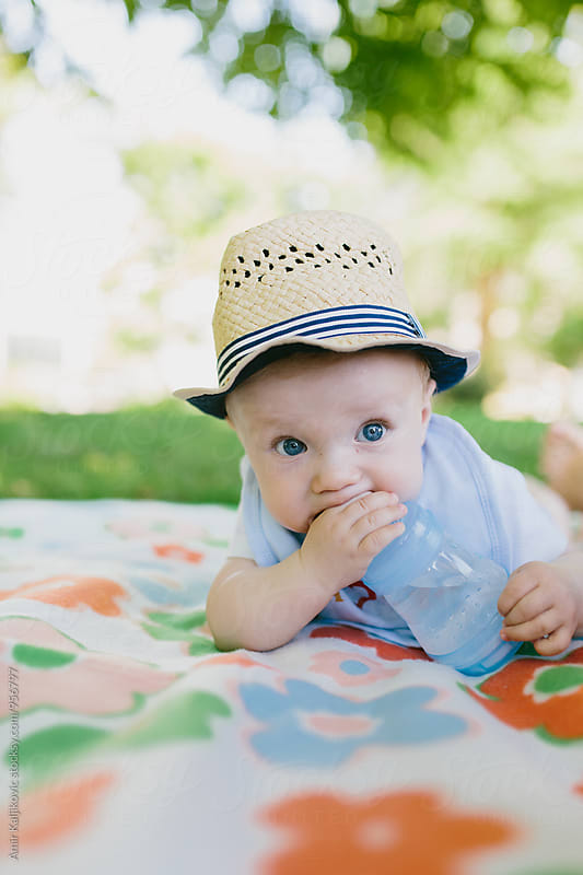 Cute baby boy in a trendy hat by Amir Kaljikovic for Stocksy United