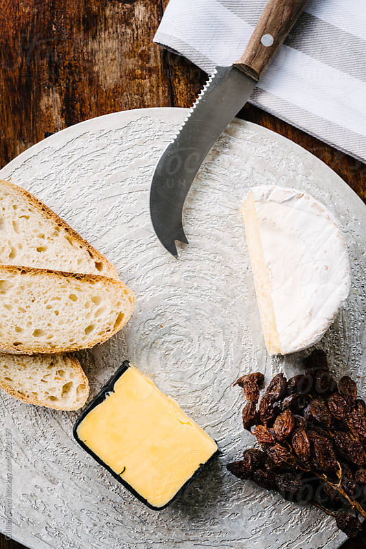 cheese platter with two cheeses, a cheddar, and brie with sliced bread and dried muscatels by Gillian Vann for Stocksy United