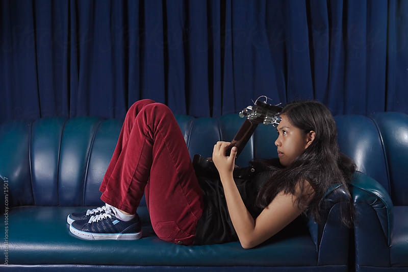 Asian Teen Girl Playing Guitar in a Makeshift Recording Studio by Joselito Briones for Stocksy United