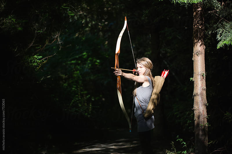 Woman aiming with archery in the wood by michela ravasio for Stocksy United