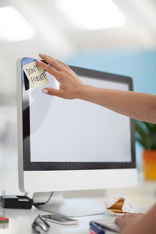 Woman sticking post it reminder on her desktop monitor. by Mosuno for Stocksy United