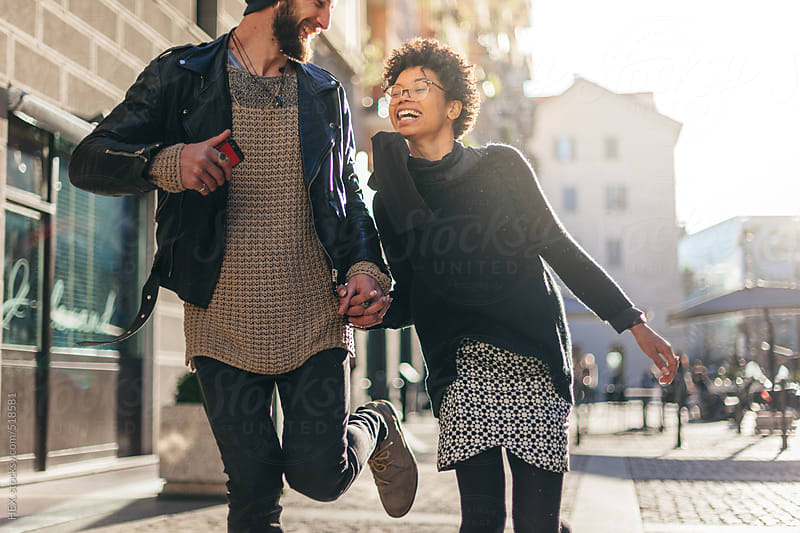 Young Couple Walking on the Street with Mobile Phone by HEX. for Stocksy United
