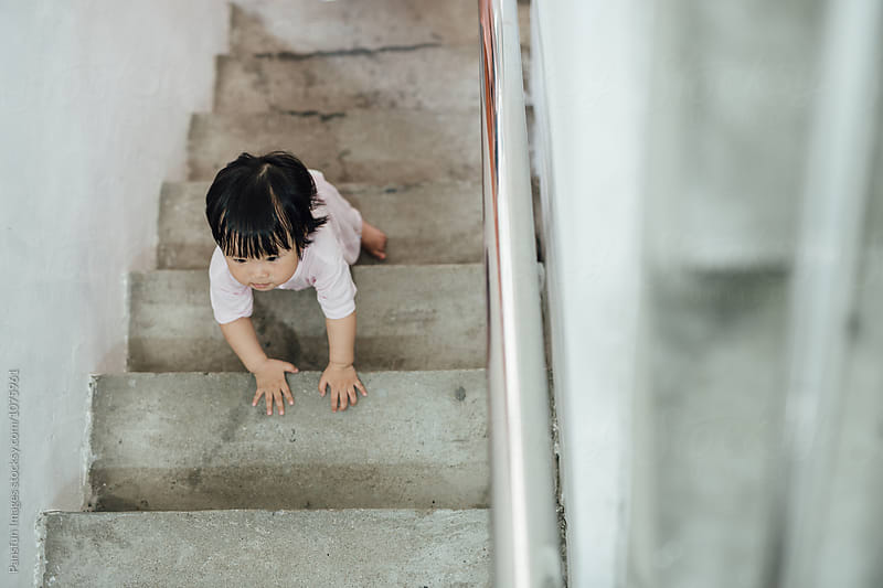 baby learning climb stairs by Xunbin Pan for Stocksy United