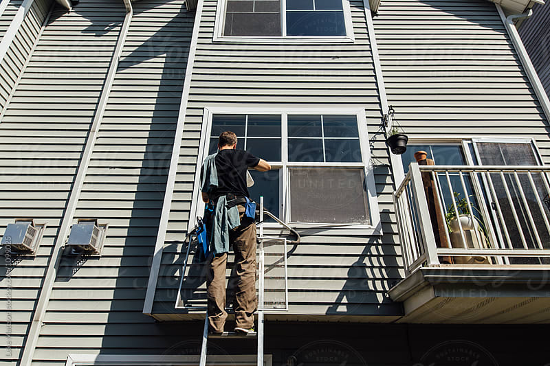 Window Washer On Ladder Outside Of Condominium Cleaning Exterior by Luke Mattson for Stocksy United