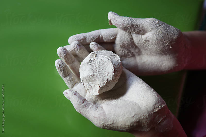 Clay Covered Hands Holding Ball of Clay by Dina Giangregorio for Stocksy United