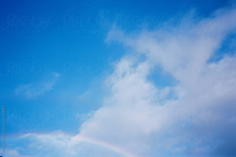 rainbow in blue sky by wendy laurel for Stocksy United