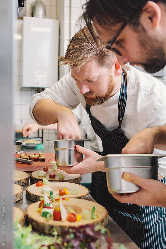Two cooks or chefs preparing the main course in a professional kitchen by Ivo de Bruijn for Stocksy United