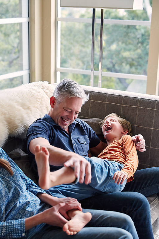 Portrait of father and son having fun and connecting in living room by Trinette Reed for Stocksy United