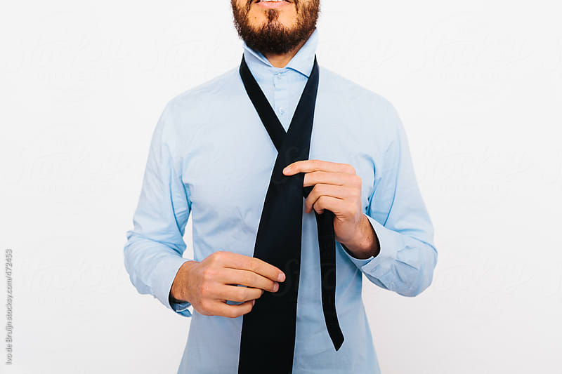 Close up of a young businessman with a beard tying his tie by Ivo de Bruijn for Stocksy United