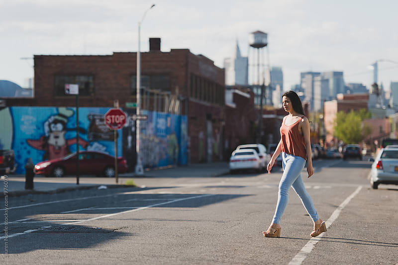 Young woman crossing the street by Lauren Naefe for Stocksy United