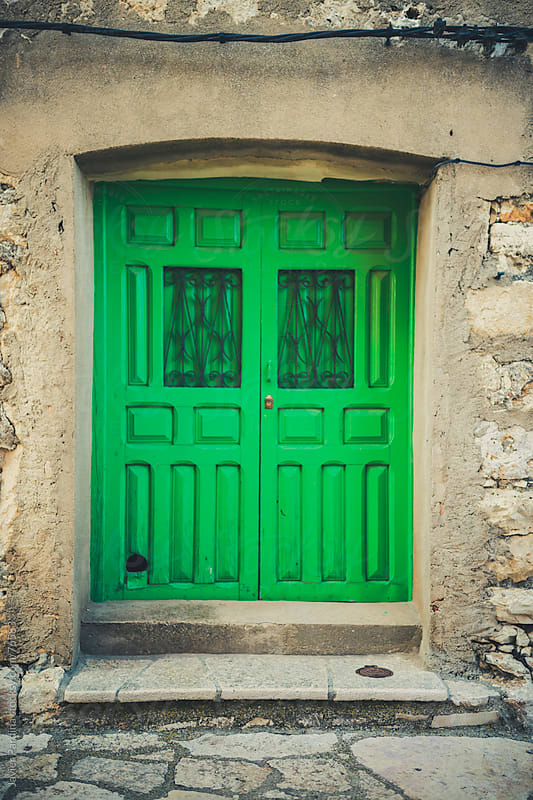 curious green door in the city by Javier Pardina for Stocksy United