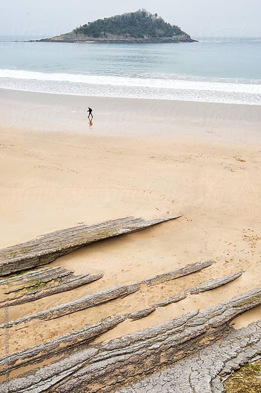 Aerial view of a man walking alone in sandy beach by Bisual Studio for Stocksy United