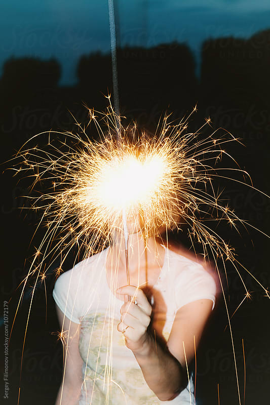 Anonumous woman posing with burning sparkler in night  by Sergey Filimonov for Stocksy United