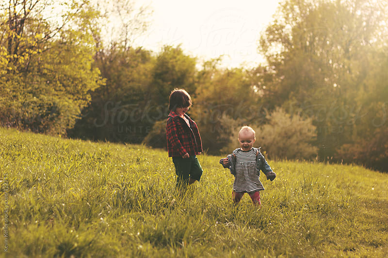 Brother and Sister Playing Outside in the Sun by Kevin Keller for Stocksy United