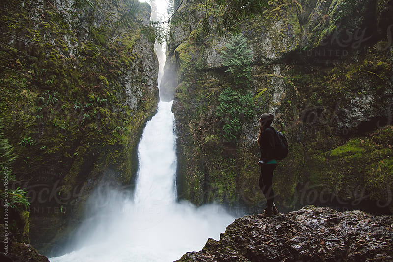 Young woman exploring a beautiful waterfall on a hike. by Kate Daigneault for Stocksy United