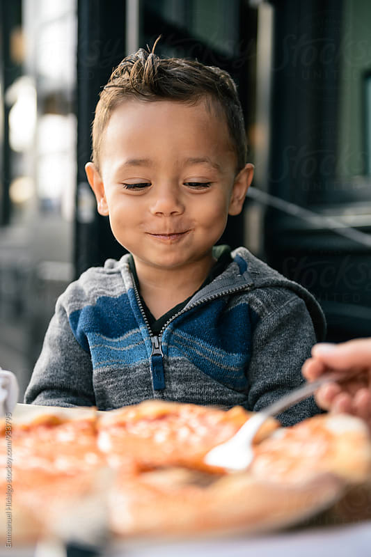 Toddler looking at his pizza that he's ready to devour by Emmanuel Hidalgo for Stocksy United