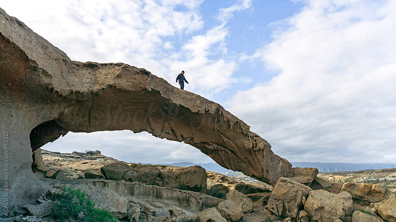 Man walking on a natural rock arch by ACALU Studio for Stocksy United