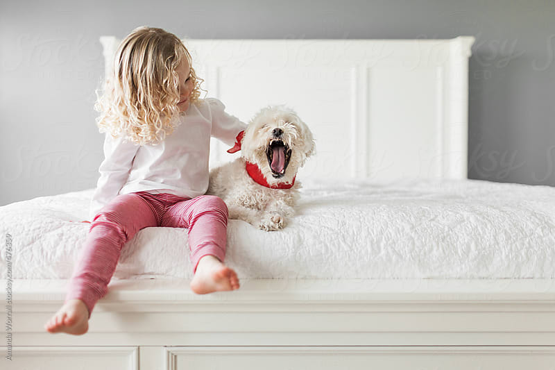 Young girl wearing red and white striped leggings pets a yawning dog  by Amanda Worrall for Stocksy United