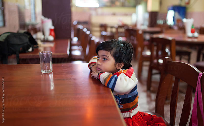 Cute toddler sitting at a restaurant waiting for dinner by Saptak Ganguly for Stocksy United