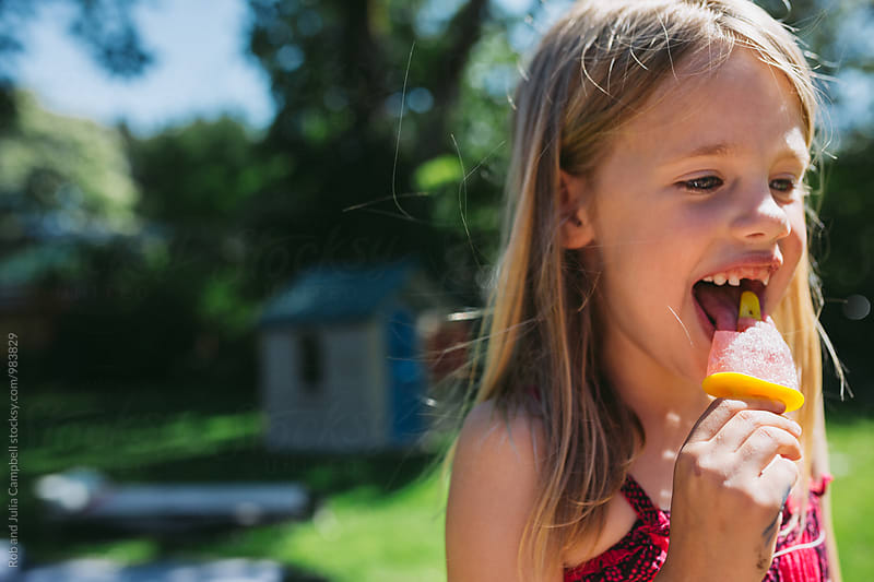 Cute young caucasian girl enjoying popsicle outside in summer by Rob and Julia Campbell for Stocksy United