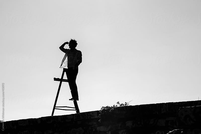 Man On Ladder Looking For Work In The City by Cameron Whitman for Stocksy United