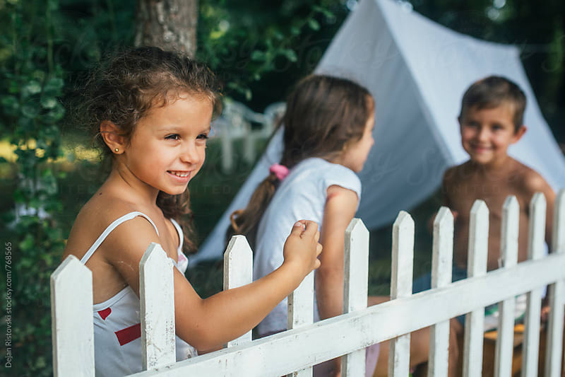 Children playing in teepee tent in backyard by Dejan Ristovski for Stocksy United