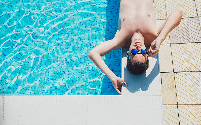 Man Lying on Edge of the Swimming Pool by Lumina for Stocksy United