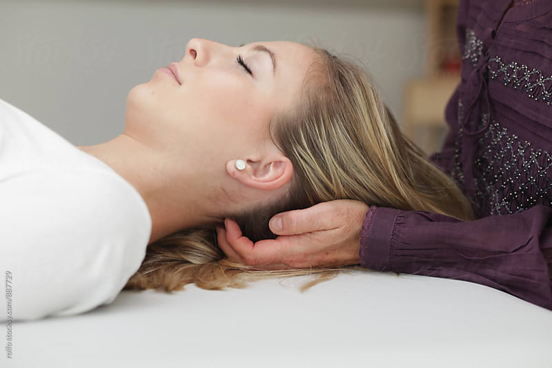 Therapist's hands massaging woman's head and neck by rolfo for Stocksy United