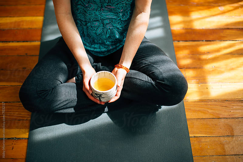 Woman sitting on yoga mat with teacup by Abby Mortenson for Stocksy United