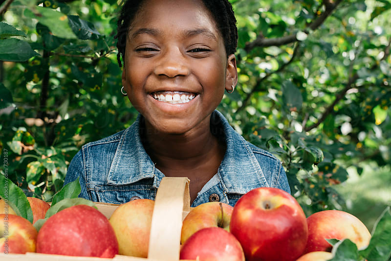Smiling black girl with freshly picked apples by Gabriel (Gabi) Bucataru for Stocksy United
