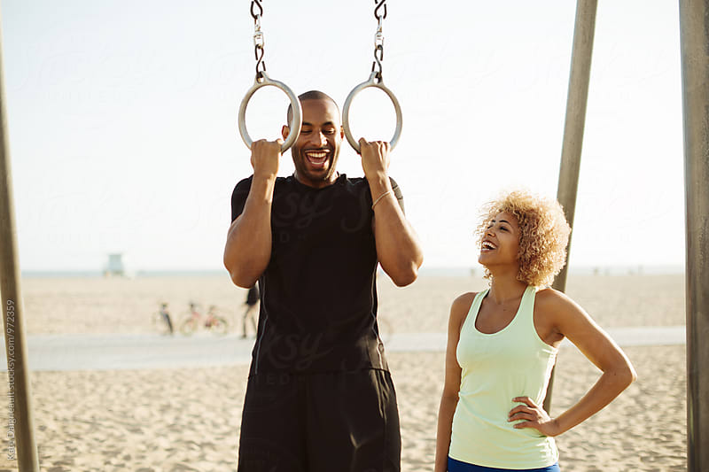Cute African American couple workout together by the beach. by Kate Daigneault for Stocksy United