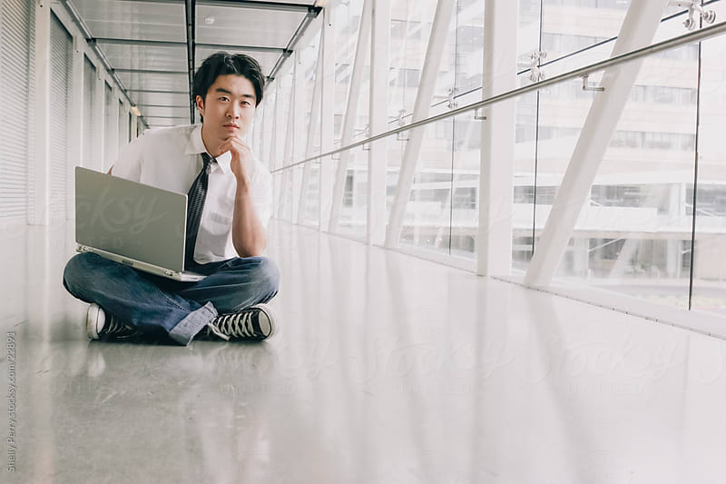 Casual Young Asian Business Man Sitting in a White Space with a Laptop by Shelly Perry for Stocksy United